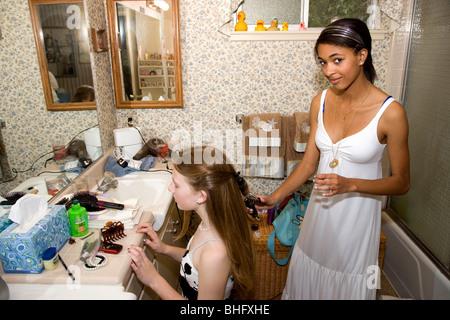 Preparando para su Baile Formal, African American Girl haciendo sus amigos de cabello en el baño, sobre sus rodillas. Foto de stock
