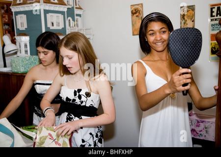 Preparando para su Baile Formal, cinco niñas multiétnica poniendo en maquillaje y haciendo su cabello en el baño. Foto de stock
