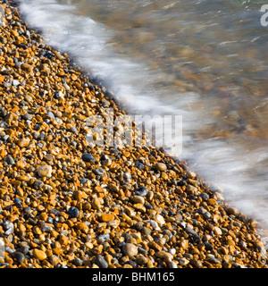 Hastings, East Sussex, Inglaterra. Guijarros Sol Bañada por la marea entrante.