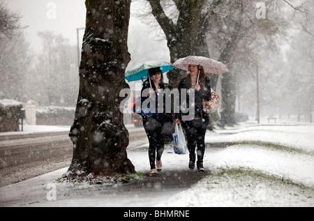 Dos chicas caminando por una tormenta de nieve en Malvern, REINO UNIDO Foto de stock