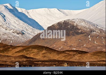 Mirando sobre Lochan na h-Achlaise hacia las laderas cubiertas de nieve de Clach Leathad (Rannoch Moor). Foto de stock