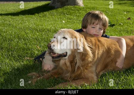 Niño y perro descansando en el césped Foto de stock