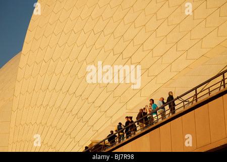 Los turistas en la parte delantera del techo gigante de la famosa ópera de Sydney, New South Wales, Australia
