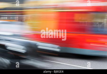 Taxis y autobuses rojos de dos pisos conduciendo por las calles de Londres, movimiento borrosa, transporte transporte el tráfico de la ciudad de Rojo negro