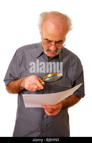 Viejo hombre intentando leer pequeños imprimir utilizando una lupa y gafas