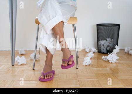 Los pies femeninos en chanclas con papeles arrugados