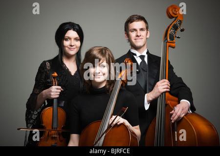 Retrato de estudio de tres músicos jóvenes con instrumentos