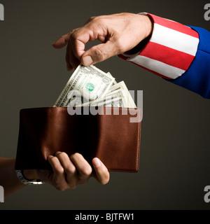 El hombre en el traje del Tío Sam toma el dinero del monedero, Foto de estudio
