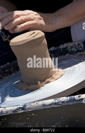 Cerca de la taza está creado de arcilla por el artista en torno de alfarero