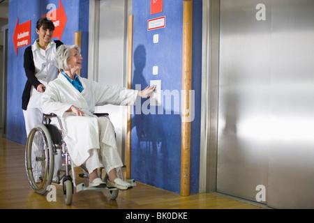 Una anciana en una silla de ruedas y una enfermera Foto de stock