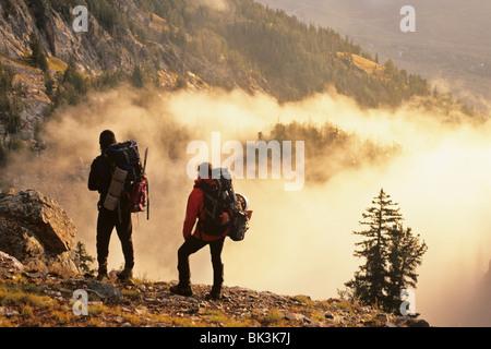 Dos alpinistas arriba pausa de niebla por la mañana temprano en la quebrada glaciar debajo de Grand Teton Pico en parque nacional Grand Teton, Wyoming.