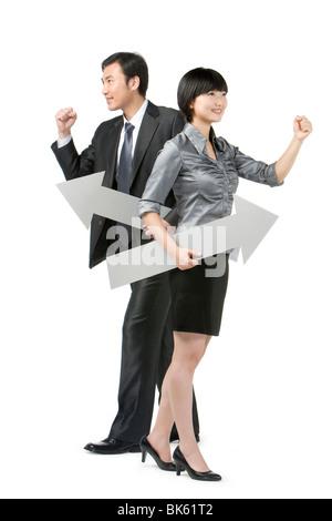 Joven Empresaria y el empresario sosteniendo flechas