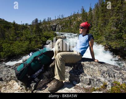 Mujer joven, excursionistas, mochileros, mochila, sentado sobre una roca, descansando, Moose Creek Canyon, detrás de la cascada, el histórico Chilkoot Pas