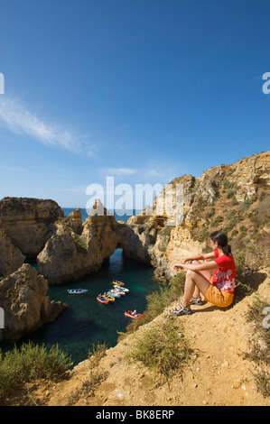 Mujer mirando hacia Ponta da Piedade, cerca de Lagos, Algarve, Portugal, Europa