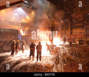Los trabajadores con acero fundido en la planta