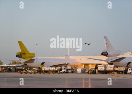 Avión de carga siendo cargado al amanecer, desde el aeropuerto de Miami, Florida, EE.UU.
