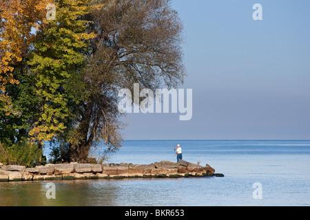 Un pescador solitario casting en el Lago Ontario, en el otoño, con coloridos árboles reflejando en el agua Foto de stock