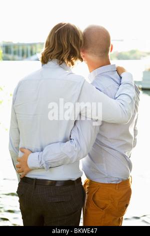 Dos hombres gay de pie a la orilla del agua
