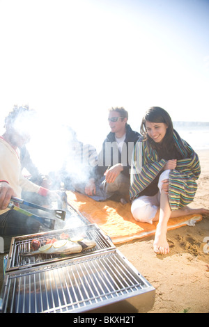 Grupo de Amigos sentados alrededor de una barbacoa en la playa Foto de stock