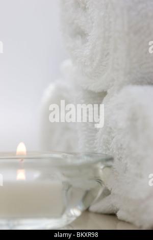 Cierre de un té ardiente luz y enrolla toallas blancas