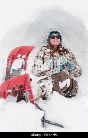 Mujer joven descansa en la nieve con raquetas de nieve en Milcreek Canyon, Salt Lake City, Utah.
