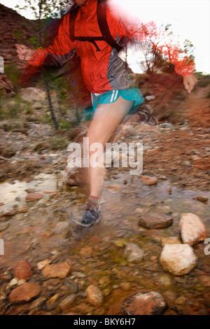 Una mujer trail running a través de una secuencia de rocas en Nevada.