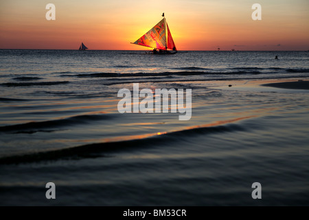 Un bote de vela pasa el atardecer en la Playa Blanca, Boracay, el destino turístico más famoso en Filipinas. Foto de stock