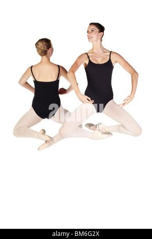 Los jóvenes caucásicos bailarinas sobre fondo blanco y blanco reflectante piso Foto de stock