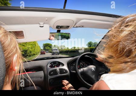 Open top coche con conductor y pasajero femenino en carretera abierta