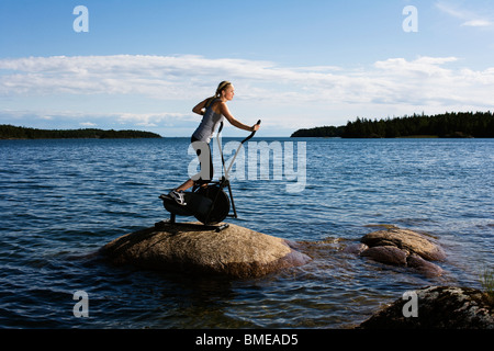 Mujer joven en un trabajo sobre una roca en un lago, Suecia.