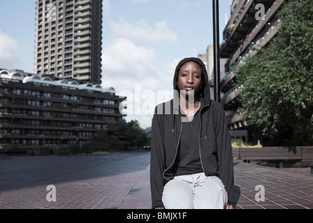 Retrato de una mujer joven se sentaba fuera de la ciudad en la urbanización.