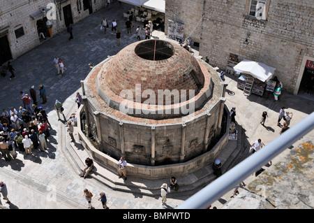 Los turistas se reúnen alrededor de la fuente de Onofrio grande en el casco antiguo de Dubrovnik.