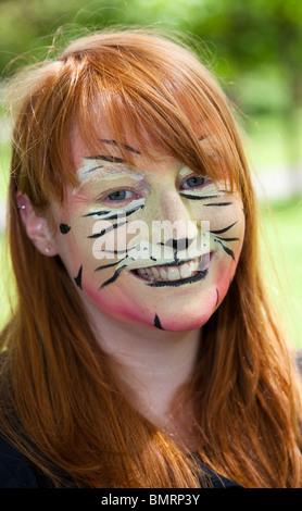 Joven con la cara pintada para parecerse a un tigre en el West End Festival celebrado en el parque Kelvingrove, Foto de stock