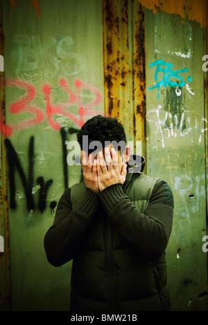 Hombre escondido rostro en manos al aire libre Berlín ALEMANIA