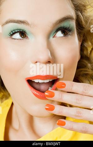 Sorprendido joven mujer rubia contra un fondo de color amarillo Foto de stock