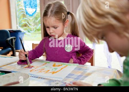 Chico y chica pintando en el kindergarten