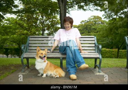 Hombre sentado en una banca del parque con su perro junto a él