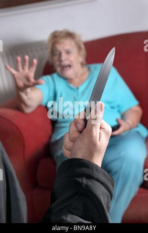 Cuchillo tirado como aterrorizado anciana mira hacia el atacante