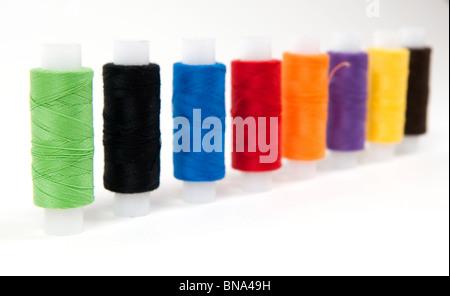 Conjunto de hilos de coser sobre fondos blancos