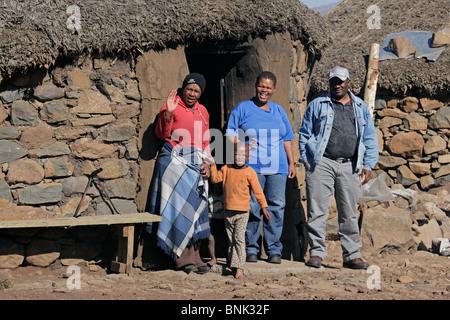 Basotho familia delante de una choza tradicional en las altas montañas Maluti del Reino de Lesotho, en el sur de Foto de stock