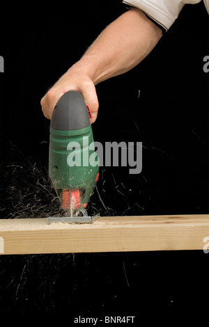 Un hombre usando una sierra de calar eléctrico para cortar un tablón de madera