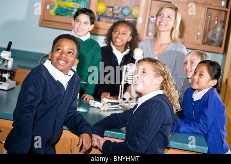 Los estudiantes de escuela primaria y profesor en el laboratorio de ciencias mirando hacia arriba