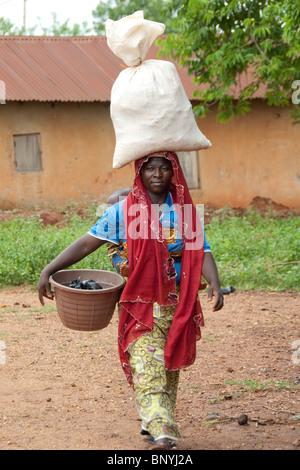 África, Togo, Kpalime Valle. Rural pueblo togolés. Mujer local en los coloridos adornos con carga en la cabeza.