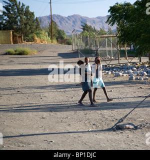 Dos niñas y bebé en camino de ripio en Aus, Namibia