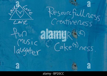 Divertido graffiti en una pared azul ensalzando el amor divertida música y risas. Y cerveza. Todo lo que necesitamos para un mundo mejor.