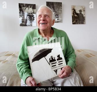 Senior Citizen fotógrafo que está teniendo una exposición de sus fotografías tomadas en el 1960.
