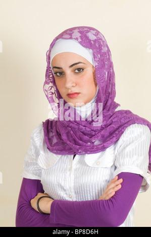 Grave joven mujer musulmana brazos plegables Foto de stock