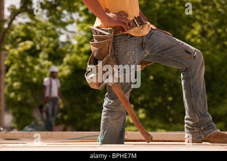 Carpintero de pie en un sitio en construcción