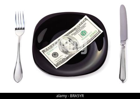 Billetes de cien dólares sobre una placa negra con cuchillo y tenedor Foto de stock
