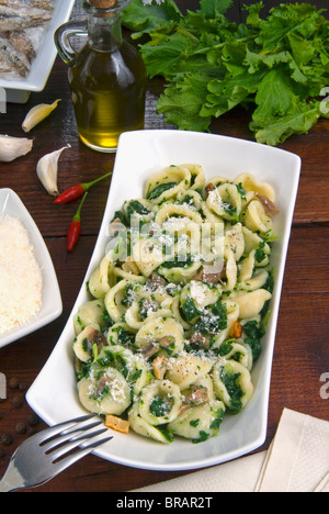 Orecchiette (poco en los oídos), un tipo de pasta de Apulia, con brócoli rabe y pescado salado (Orecchiette con cime di rapa), Italia